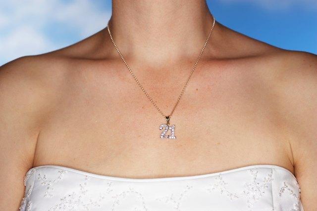 Bride wearing twenty first birthday motif necklace, close-up