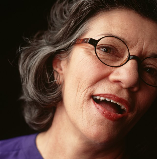 Woman with dark hair and spectacles, posing in studio, close-up, portrait