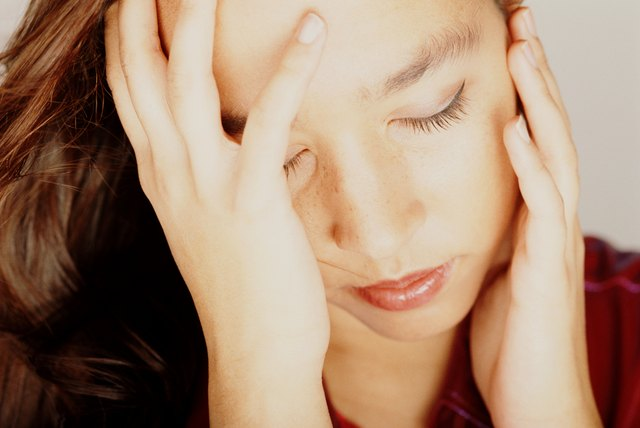 Young woman with eyes closed, head in hands, close-up