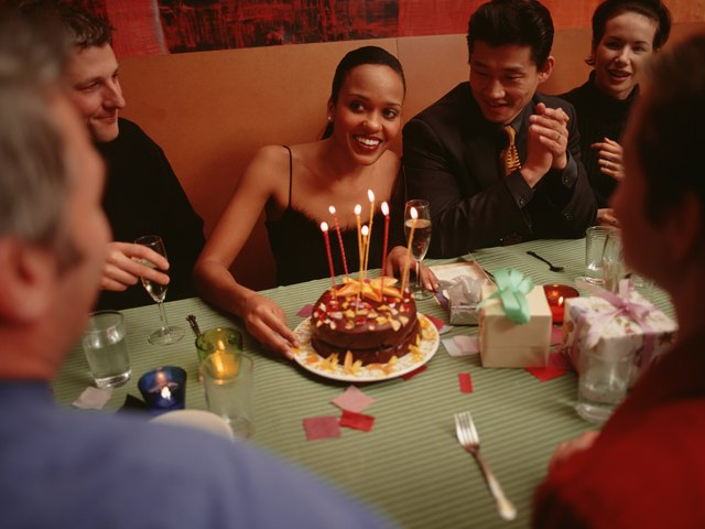 Group of people celebrating birthday party in restaurant
