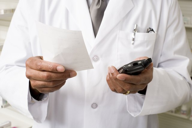 Pharmacist holding prescription and portable communication device