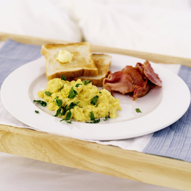 Close-up of scrambled eggs served with bacon and toast