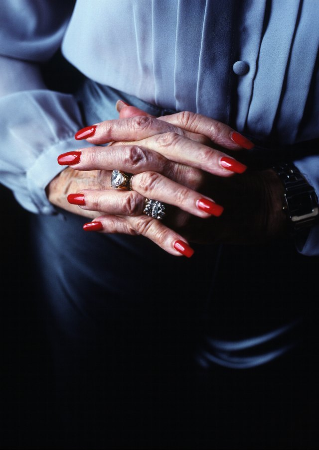 close-up of an elderly woman's hands with nails painted red