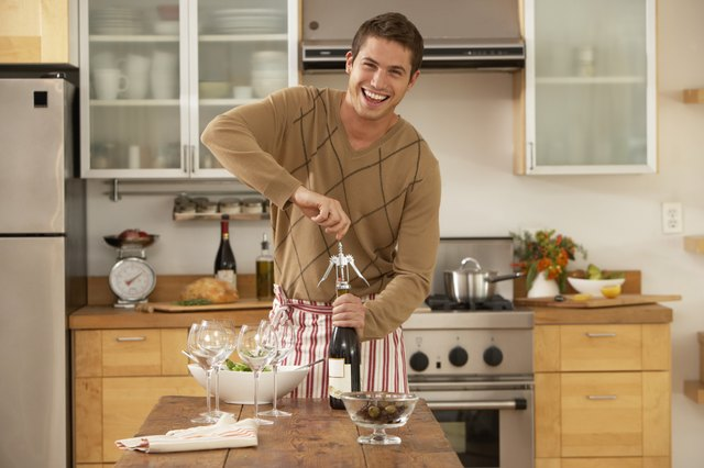 Man in kitchen opening bottle of wine, smiling, portrait
