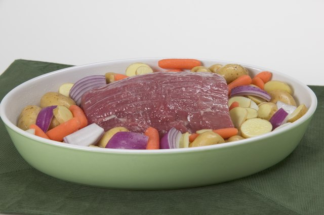 Uncooked pot roast on a bed of vegetables