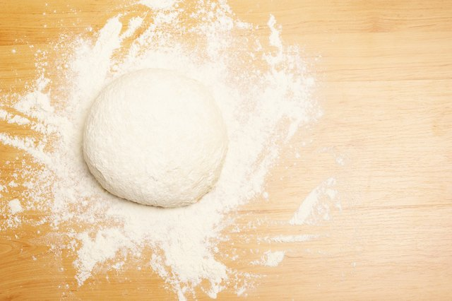 Ball of dough with flour on wooden surface
