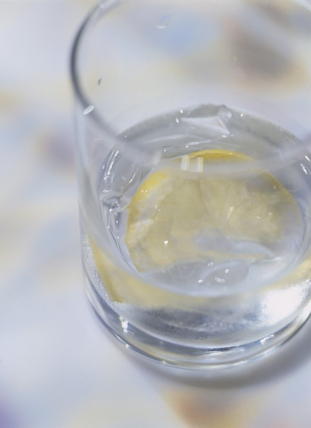 close-up of a glass of ice water and a slice of lemon