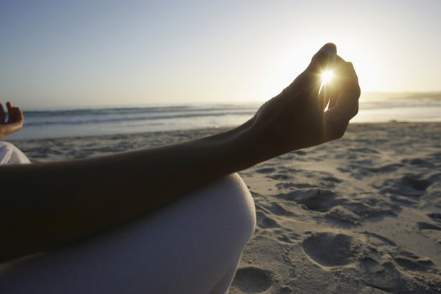 Woman meditating on beach at sunrise