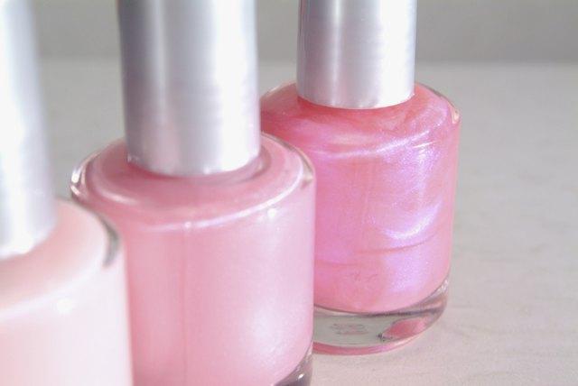 Close-up of three bottles of pink nail polish