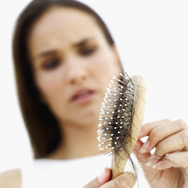 close-up of a young woman removing hair from a hairbrush