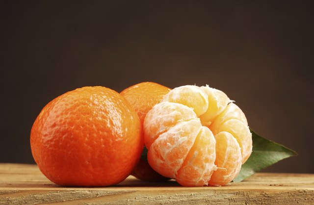 tangerines with leaf on wooden table on brown background