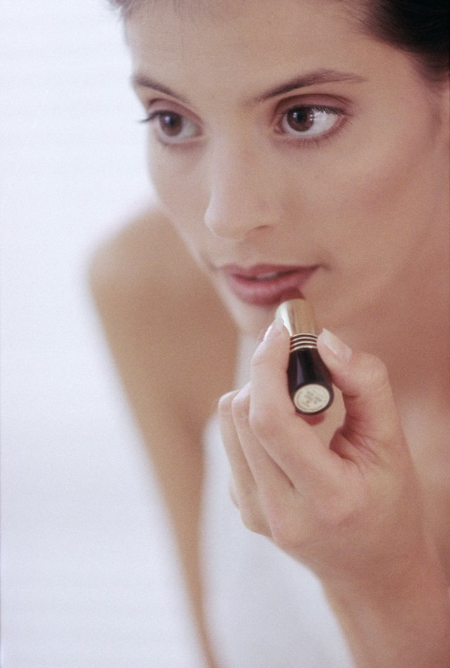 Close-up of a young woman applying lipstick to her lips