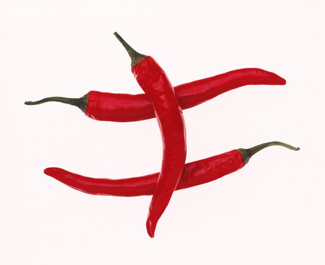 Three red chilli pepper on white background, close-up