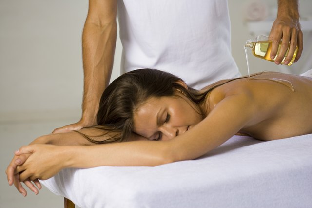 Masseur pouring massage oil on the back of a woman