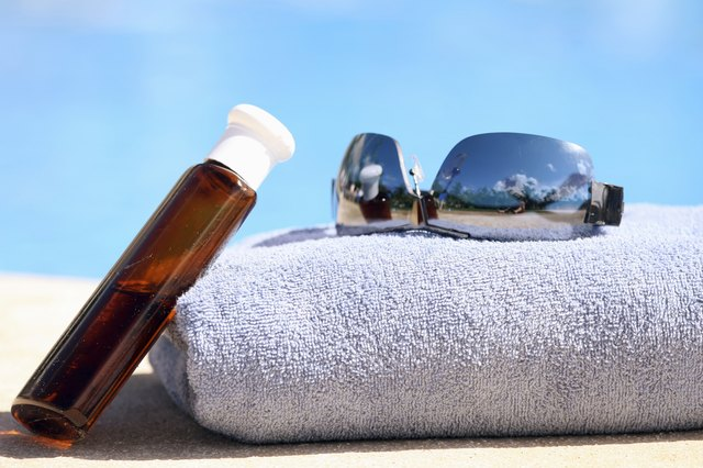 Sunglasses, towel and oil bottle