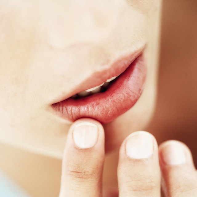 Close-up of a young woman touching her lip