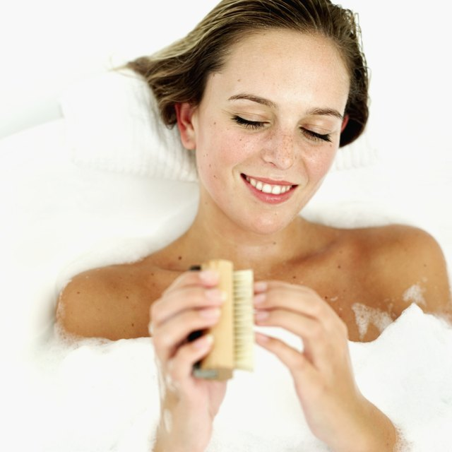 Young woman buffing her nails in a bubble bath