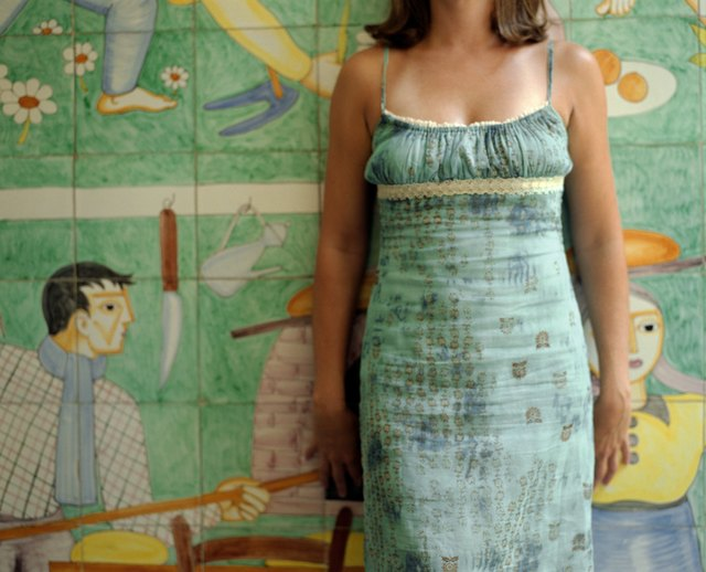Woman in sundress standing by mural painting