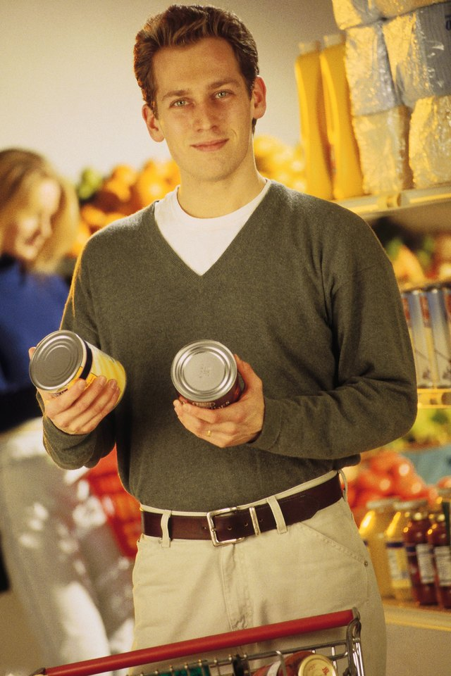 Young man holding canned food in grocery aisle