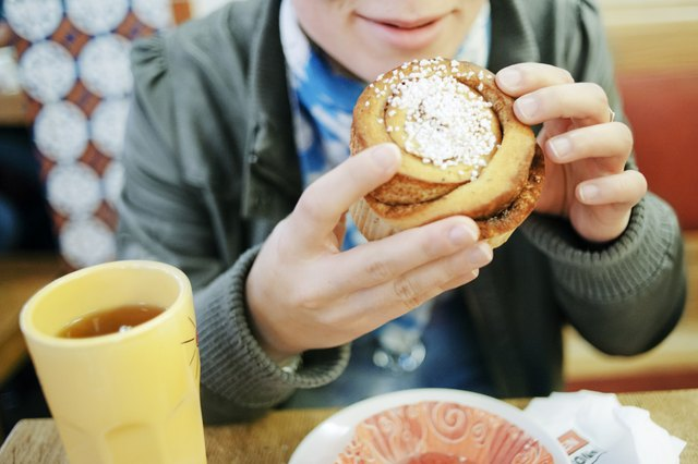 Sweden, Vastra Gotaland, Goteborg, Young woman eating cinnamon bun