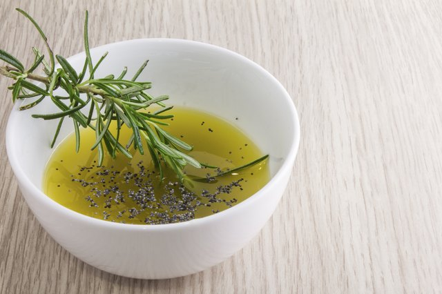 rosemary oil sauce in bowl on wood background