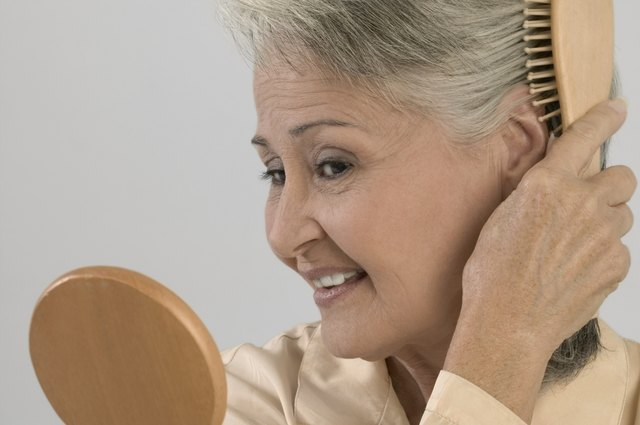 Portrait of senior woman holding mirror and brushing hair