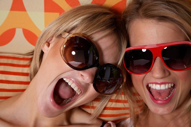 Two young women wearing sunglasses, yelling, close-up
