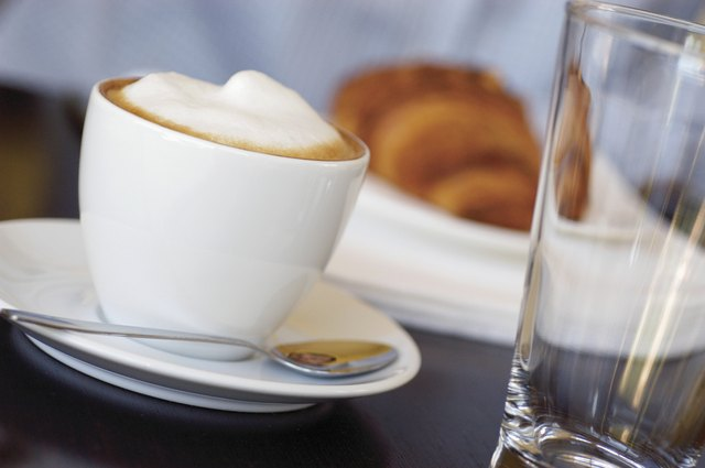Cup of cappuccino on saucer with spoon, croissant and empty glass