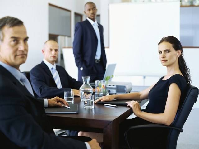 Portrait of three businessmen and a businesswoman in a meeting