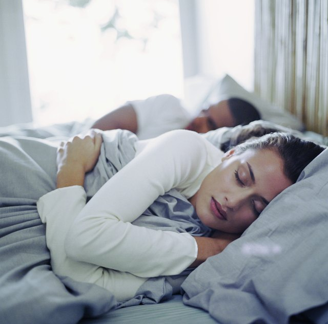 Young man and woman sleeping in bed (focus on woman)