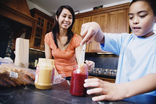 Mother and son making peanut butter and jelly sandwich