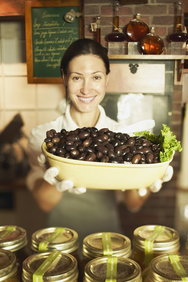 Woman holding large bowl of black olives
