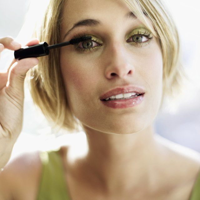 portrait of woman applying eye makeup