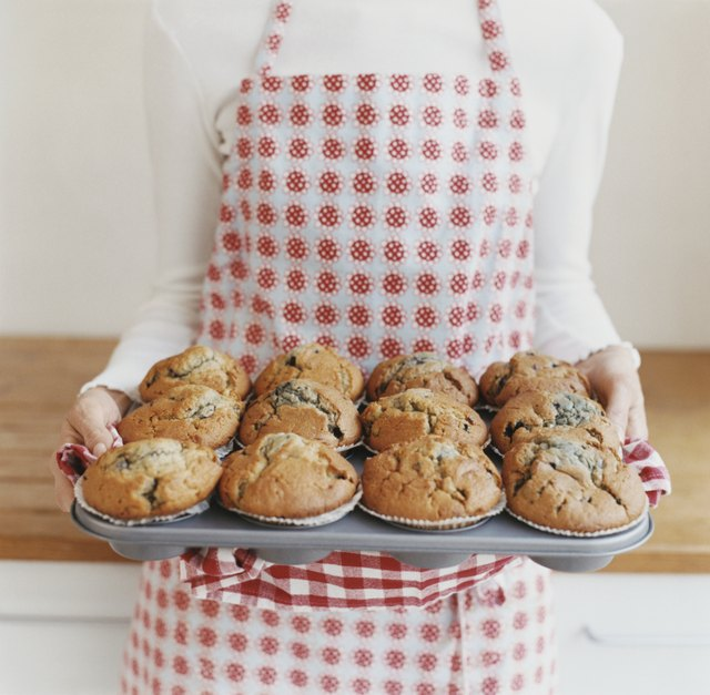 Mid Section View of a Woman Carrying a Baking Tray With Muffins