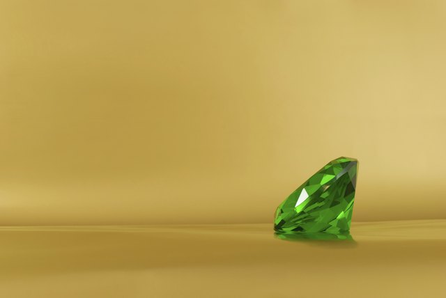 Green emerald gem on a golden background with copy space