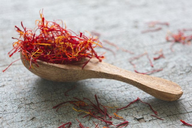 Spoon Of Saffron On Old Wooden Surface