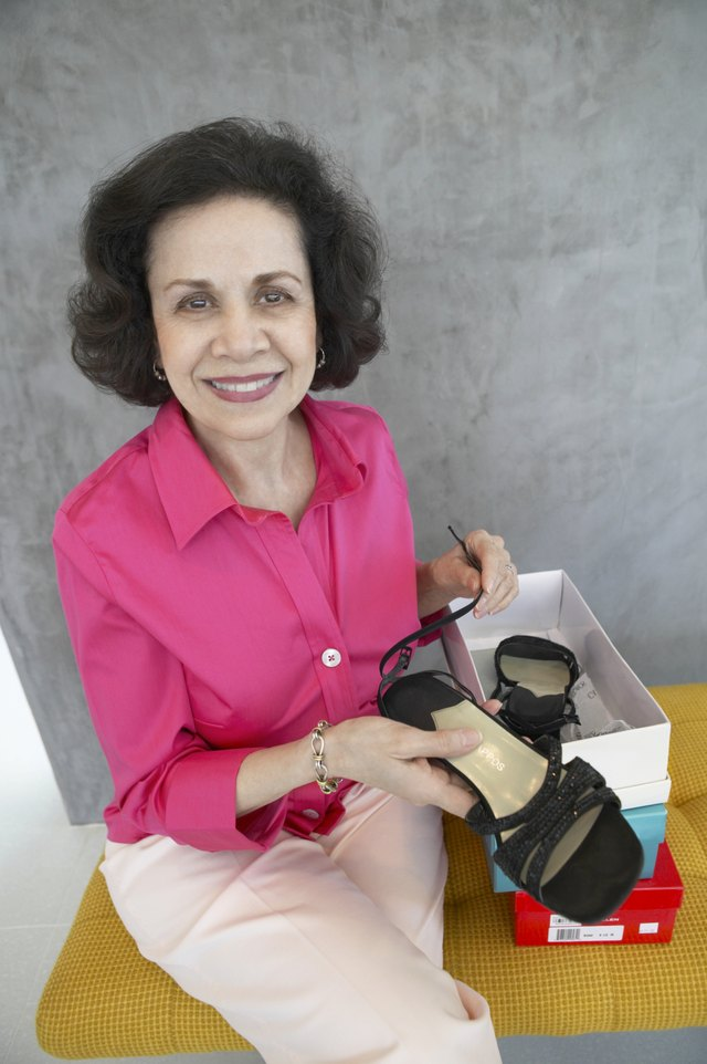 Portrait of a Mature Woman Sitting on a Bench in a Shoe Shop Holding a Pair of Shoes