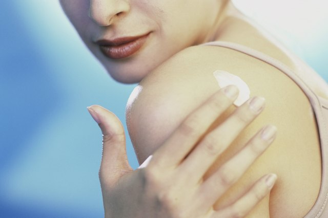 Close-up of a young woman applying moisturizer on her shoulder