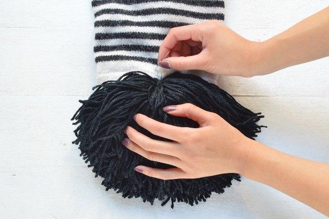 Sew the pom-pom to the scarf